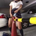 schoolgirl ruding a traffic cone